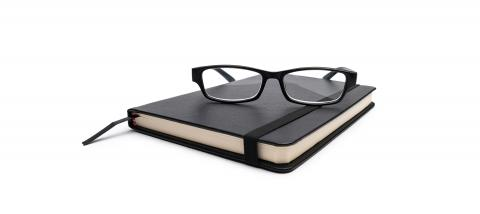 closed black cover notebook with glasses on white  background- Stock Photo or Stock Video of rcfotostock | RC-Photo-Stock