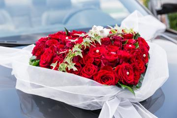 A stylish decoration of red rose flowers, ribbons on a shiny black wedding car : Stock Photo or Stock Video Download rcfotostock photos, images and assets rcfotostock | RC-Photo-Stock.: