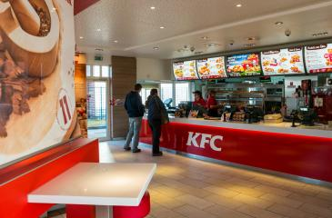 AACHEN, GERMANY FEBRUARY, 2017: People Order Kentucky Fried Chicken In Fast-Food Restaurant. It is a fast food restaurant chain headquartered in United States specialized in chicken products.- Stock Photo or Stock Video of rcfotostock | RC-Photo-Stock
