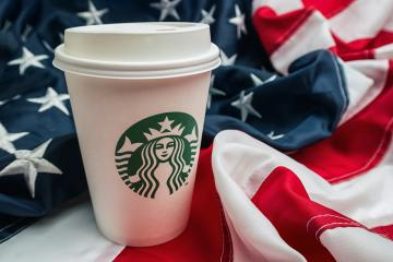 AACHEN, GERMANY FEBRUARY, 2017: Starbucks take away coffee cup on a america flag.  Starbucks is the largest coffeehouse company in the world.- Stock Photo or Stock Video of rcfotostock | RC-Photo-Stock