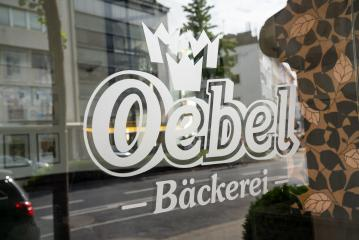 AACHEN, GERMANY JULY 2019:  Oebel bakery Store Logo on a glass window. Headquartered in Aachen, Oebel is a bakery company since 1918, with bakeries and bakery cafes in Aachen and around NRW.- Stock Photo or Stock Video of rcfotostock | RC-Photo-Stock