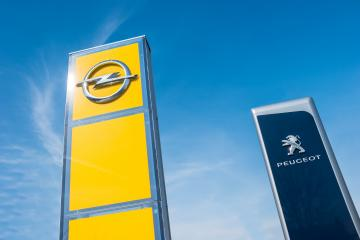 AACHEN, GERMANY MARCH, 2017: Peugeot and Opel dealership sign against blue sky. Peugeot is a French automobile manufacturer and part of Groupe PSA. Opel AG is a German automobile manufacturer.- Stock Photo or Stock Video of rcfotostock | RC-Photo-Stock