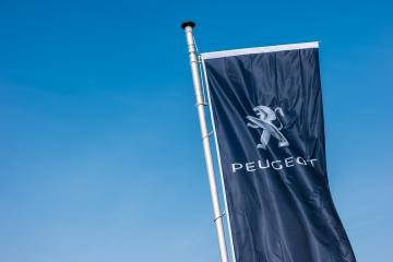 AACHEN, GERMANY MARCH, 2017: Peugeot logo on a flag against blue sky. Peugeot is a French cars brand, part of PSA Peugeot Citroen.- Stock Photo or Stock Video of rcfotostock | RC-Photo-Stock