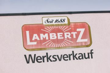 AACHEN, GERMANY OCTOBER, 2017: Lambertz Logo on a factory building. The Lambertz Group is a Aachener Printen- and chocolate factory founded by Henry Lambertz 1688 and a manufacturer Christmas cookies.- Stock Photo or Stock Video of rcfotostock | RC-Photo-Stock