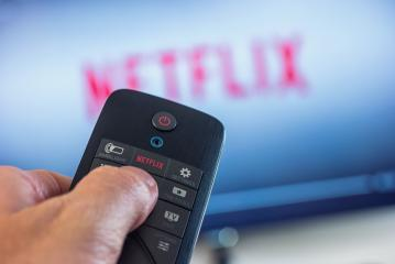 AACHEN, GERMANY OCTOBER, 2017:Man holds a remote control and selects a movie from Netflix. Netflix is an entertainment company, specializes in and provides streaming media and video on demand online.- Stock Photo or Stock Video of rcfotostock | RC-Photo-Stock