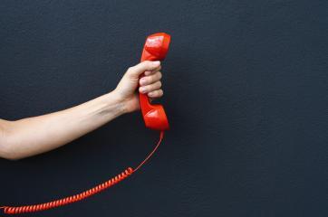 Abgeschnittene Hand einer Frau, die einen Telefonhörer an einer schwarzen Wand hält - Stock Photo or Stock Video of rcfotostock | RC-Photo-Stock