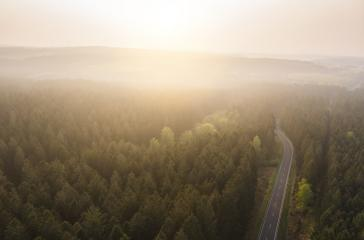 Aerial drone view of a scenic highway to the beautiful Landscape with mountains covered in clouds and fog.- Stock Photo or Stock Video of rcfotostock | RC-Photo-Stock