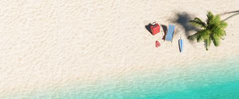 Aerial top view  of sandy beach and ocean and beach chair flip-flop sandals, umbrella and suit case under a palm tree at the beach during a summer vacation in the Caribbean, , banner size, copy space - Stock Photo or Stock Video of rcfotostock | RC-Photo-Stock