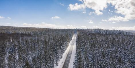 Aerial view of cars driving by the road through the forest covered by snow in winter and cloudy sky, including Copy space- Stock Photo or Stock Video of rcfotostock | RC-Photo-Stock