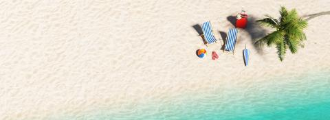 Aerial view of sandy beach and ocean and beach chair with beach ball flip-flop sandals, umbrella and suit case under a palm tree at the beach during a summer vacation in the Caribbean, with copy space- Stock Photo or Stock Video of rcfotostock | RC-Photo-Stock