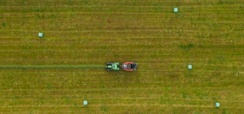Aerial view of Tractor mowing green field in summer. Drone Shot- Stock Photo or Stock Video of rcfotostock | RC-Photo-Stock