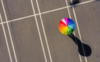 Aerial view of woman holding rainbow umbrella parking lot background - view from a drone : Stock Photo or Stock Video Download rcfotostock photos, images and assets rcfotostock | RC-Photo-Stock.:
