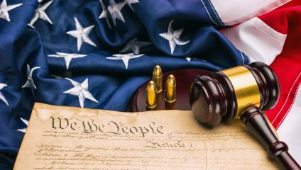 American Constitution with judge gavel and gun cartridges on a america flag- Stock Photo or Stock Video of rcfotostock | RC-Photo-Stock