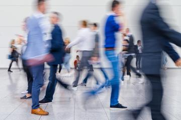 Anonymous crowd of business people go by gear on a trade fair- Stock Photo or Stock Video of rcfotostock | RC-Photo-Stock