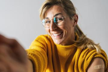 Attractive mature woman smiling after getting a corona vaccine. Woman holding up her shirt sleeve and showing her arm with bandage after receiving vaccination, stretching arm to camera for a selfie.- Stock Photo or Stock Video of rcfotostock | RC-Photo-Stock