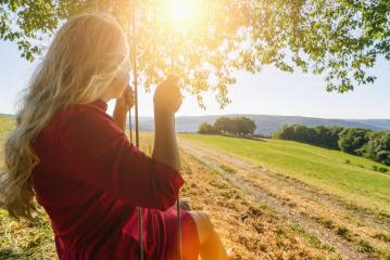 Back view of happy blond girl on swing in sun light- Stock Photo or Stock Video of rcfotostock | RC-Photo-Stock