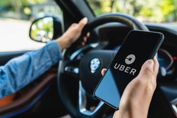 BERLIN, GERMANY JULY 2019: Uber driver holding smartphone in car. Uber is an American company offering transportation services online. Illustrative editorial.- Stock Photo or Stock Video of rcfotostock   RC-Photo-Stock