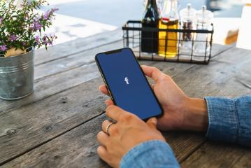 BERLIN, GERMANY JULY 2019: Woman hand holding iphone Xs with logo of Facebook application in a Restaurant. Facebook is an online social networking service founded in February 2004 by Mark Zuckerberg.- Stock Photo or Stock Video of rcfotostock | RC-Photo-Stock
