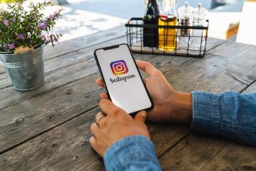 BERLIN, GERMANY JULY 2019: Woman hand holding iphone Xs with logo of instagram application in a restaurant. Instagram is largest and most popular photograph social networking.- Stock Photo or Stock Video of rcfotostock | RC-Photo-Stock