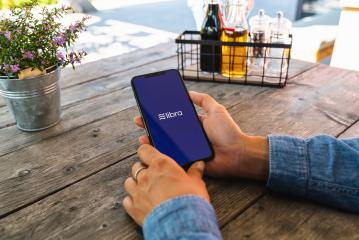 BERLIN, GERMANY JULY 2019: Woman hand holding iphone Xs with logo of Libra in a Restaurant to pay. Libra Facebook cryptocurrency and bitcoin cryptocurrency smartphone share, Libra coins concept.- Stock Photo or Stock Video of rcfotostock | RC-Photo-Stock