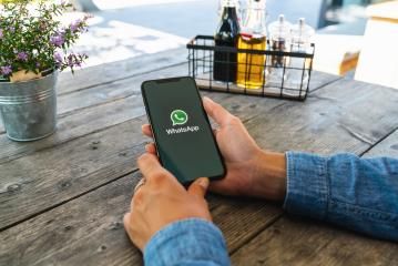 BERLIN, GERMANY JULY 2019: Woman holding a iPhone Xs opening Whatsapp app in a restaurant. WhatsApp messenger for sending messages via the Internet.- Stock Photo or Stock Video of rcfotostock | RC-Photo-Stock