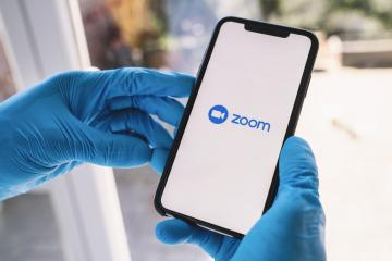 BERLIN, GERMANY MAR 2020: Man with gloves opening the Zoom mobile app on her smartphone. Zoom users can opt to record sessions, collaborate on projects, and share or annotate on one another- Stock Photo or Stock Video of rcfotostock | RC-Photo-Stock