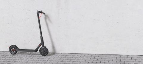 black e-scooter parked on a sidewalk at a wall for urban mobility. copyspace for your individual text.- Stock Photo or Stock Video of rcfotostock | RC-Photo-Stock