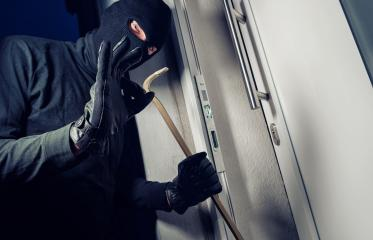 Burglar in a mask breaking Into a house with a crowbar : Stock Photo or Stock Video Download rcfotostock photos, images and assets rcfotostock | RC-Photo-Stock.:
