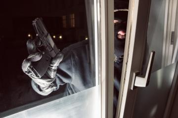 Burglar with gun looking at a window to breaking and entering a victim's home : Stock Photo or Stock Video Download rcfotostock photos, images and assets rcfotostock | RC-Photo-Stock.: