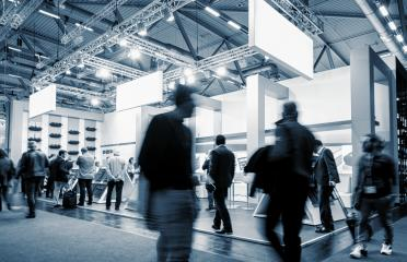 business people walking at a trade show booth at a public event exhibition hall, with banner and copy space for individual text- Stock Photo or Stock Video of rcfotostock | RC-Photo-Stock
