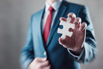 Businessman holding a puzzle to connect - Stock Photo or Stock Video of rcfotostock | RC-Photo-Stock