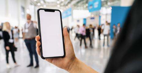 Businesswoman hand holding black cellphone with white screen at a trade fair, copyspace for your individual text.- Stock Photo or Stock Video of rcfotostock | RC-Photo-Stock