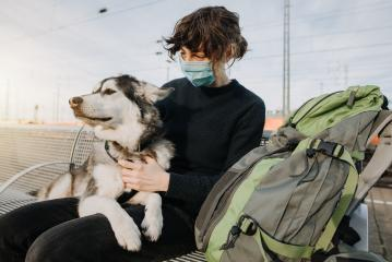 Casual Woman with backpack is waiting for the train with her dog on the platform and is wearing a face mask because of the coronavirus. Lovely  und happy friendship with your pet.- Stock Photo or Stock Video of rcfotostock | RC-Photo-Stock