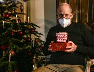 Caucasian Senior man wearing covid-19 mask sitting on chair alone holding a gift in Christmas decorated room . Coronavirus self isolation and celebrate Christmas alone concept : Stock Photo or Stock Video Download rcfotostock photos, images and assets rcfotostock | RC-Photo-Stock.: