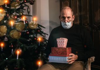 Caucasian Senior man wearing covid-19 mask sitting on chair alone holding a gift in Christmas decorated room .  : Stock Photo or Stock Video Download rcfotostock photos, images and assets rcfotostock | RC-Photo-Stock.: