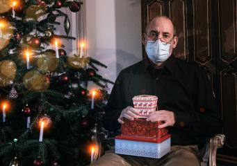 Caucasian Senior man wearing covid-19 mask sitting on chair alone holding a gift in Christmas decorated room . - Stock Photo or Stock Video of rcfotostock | RC-Photo-Stock