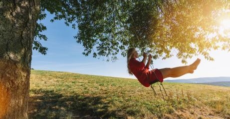 Cheerful lady in red sundress leaning back in her swing in sunny golden countryside. Evening sunshine beaming on lovely girl swaying under single tree in big green meadow- Stock Photo or Stock Video of rcfotostock | RC-Photo-Stock