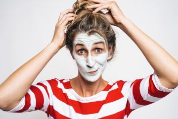 Cheerful woman correcting hair bun, has clay mask on face, enjoys softness, has beauty treatments at home, on gray background. Skin care concept image : Stock Photo or Stock Video Download rcfotostock photos, images and assets rcfotostock | RC-Photo-Stock.: