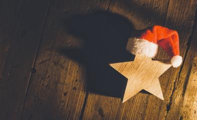 Christmas star with red santa hat on wooden background, including copy space- Stock Photo or Stock Video of rcfotostock | RC-Photo-Stock