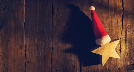 Christmas star with santa hat on wooden background, elegant low-key shot, including copy space- Stock Photo or Stock Video of rcfotostock | RC-Photo-Stock