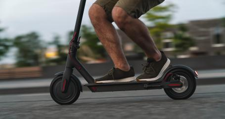 Close up of man riding black electric kick scooter at cityscape at night with motion blur- Stock Photo or Stock Video of rcfotostock | RC-Photo-Stock