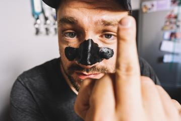 close up of man showing middle finger hand sign and black Mask Peeling cosmetic - gesture, morals and people concept- Stock Photo or Stock Video of rcfotostock | RC-Photo-Stock