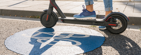 Close up of woman standing on a electric scooter or kick scooter at a blue Bicycle road sign- Stock Photo or Stock Video of rcfotostock | RC-Photo-Stock