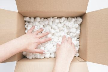 Closeup of female hands digging in a heap of packing peanuts in cardboard- Stock Photo or Stock Video of rcfotostock | RC-Photo-Stock