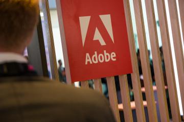 COLOGNE, GERMANY SEPTEMBER, 2017: Adobe Systems Logo with business man. Adobe is a multinational software company that produces and sells multimedia and creativity software.- Stock Photo or Stock Video of rcfotostock | RC-Photo-Stock