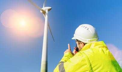 construction worker inspecting wind turbine, speaking with Walkie Talkie- Stock Photo or Stock Video of rcfotostock | RC-Photo-Stock