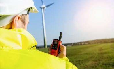 Construction worker with helmet using walkie-talkie to inspecting a wind turbine, copyspace for your individual text.- Stock Photo or Stock Video of rcfotostock | RC-Photo-Stock
