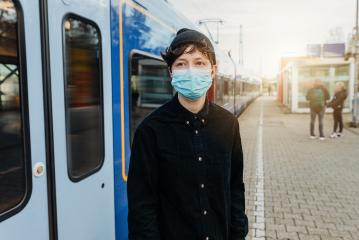 Coronavirus, COVID-19. Young modern man with medical face mask to protect against the coronavirus while waiting for the train on the subway platform. Mouth protection obligation at the train station : Stock Photo or Stock Video Download rcfotostock photos, images and assets rcfotostock | RC-Photo-Stock.: