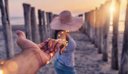 Couple holding hands and walking on beach in sunset, woman with white shirt and shorts jeans- Stock Photo or Stock Video of rcfotostock | RC-Photo-Stock