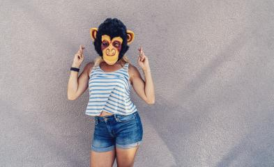 Crazy young woman with monkey mask stands on a gray wall and and cross fingers. copyspace for your individual text. - Stock Photo or Stock Video of rcfotostock | RC-Photo-Stock